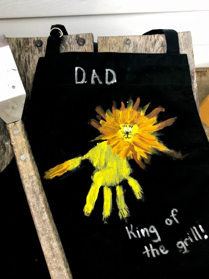 A lion painted on an apron close up made from a child\'s handprint wit a grill brush laying next to it.