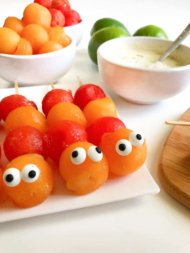 Close up of melon balls decorated to look like caterpillars on sticks