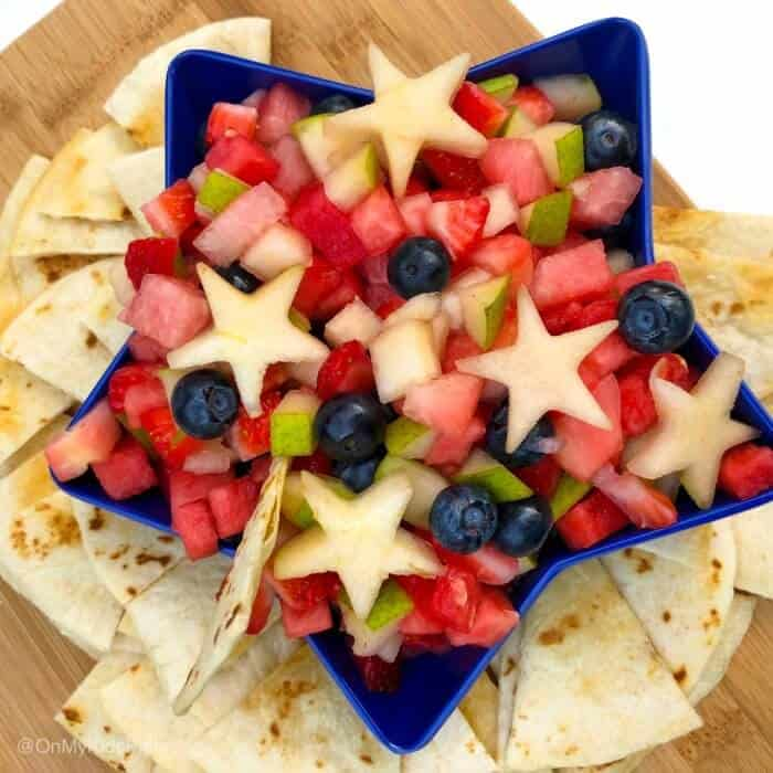 A star-shaped bowl full of fruit salsa with chips around the bowl