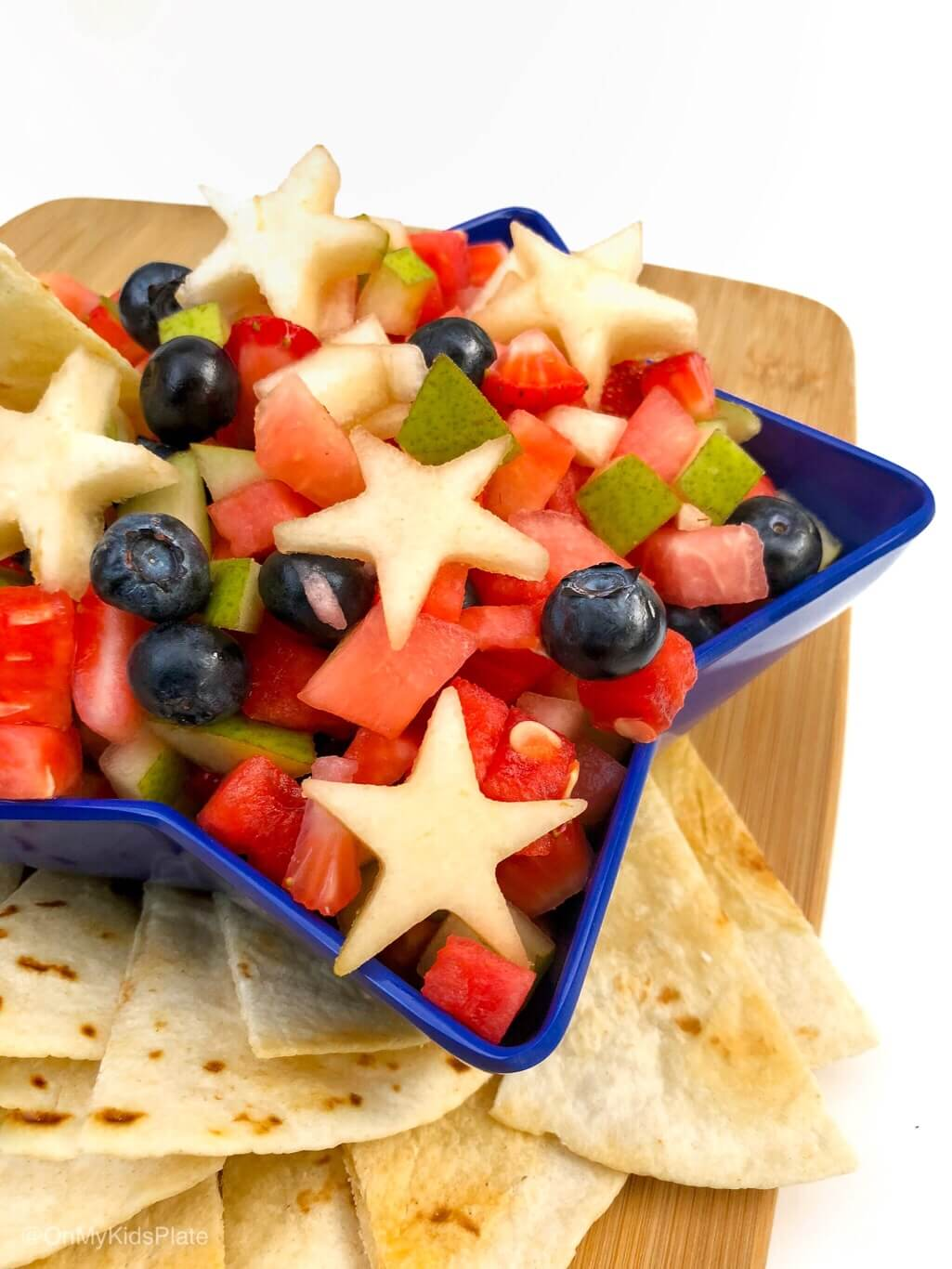 Close up of a star-shaped bowl full of fruit with chips nearby