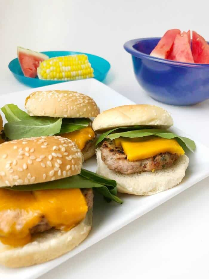 A platter of sliders with corn and watermelon in the background