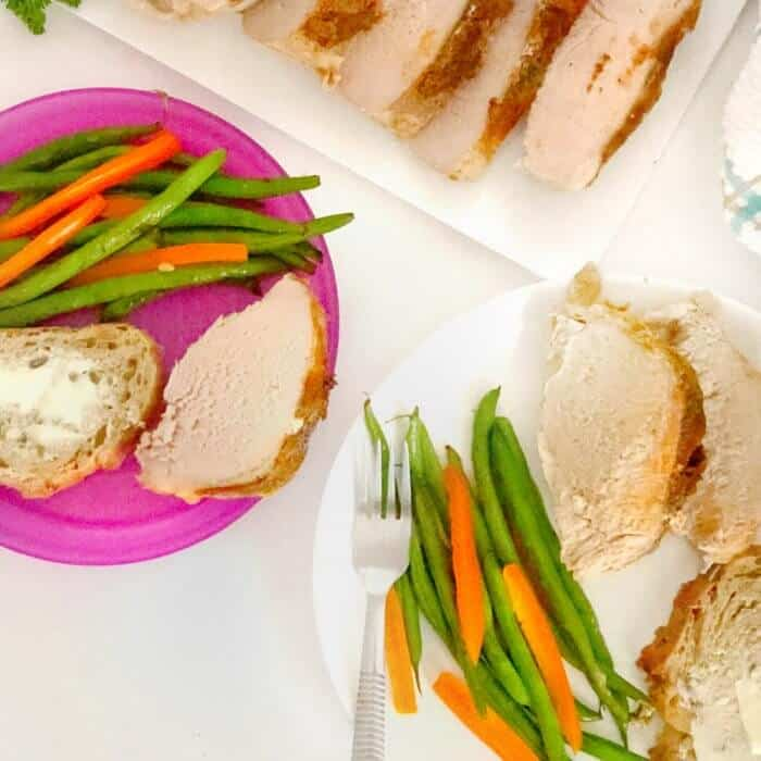 A platter of pork loin sliced next to an adult and kids purple dinner plate with vegetables and bread