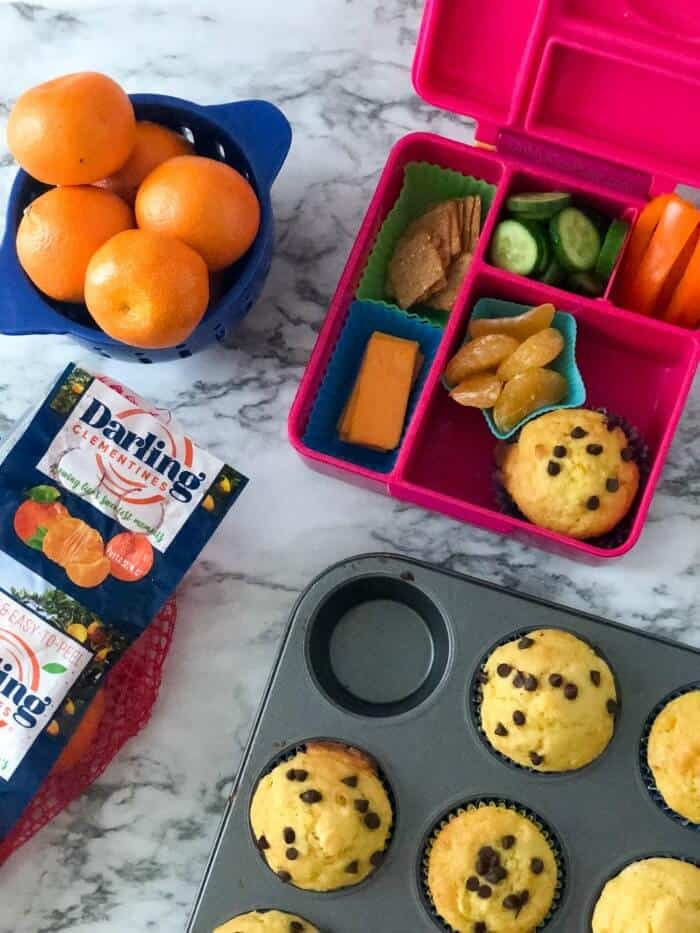 An overhead cview of a child\'s lunchbox being packed with fruits, vegetables cheese and orange muffins next to more oranges in a bowl and muffins in a pan.