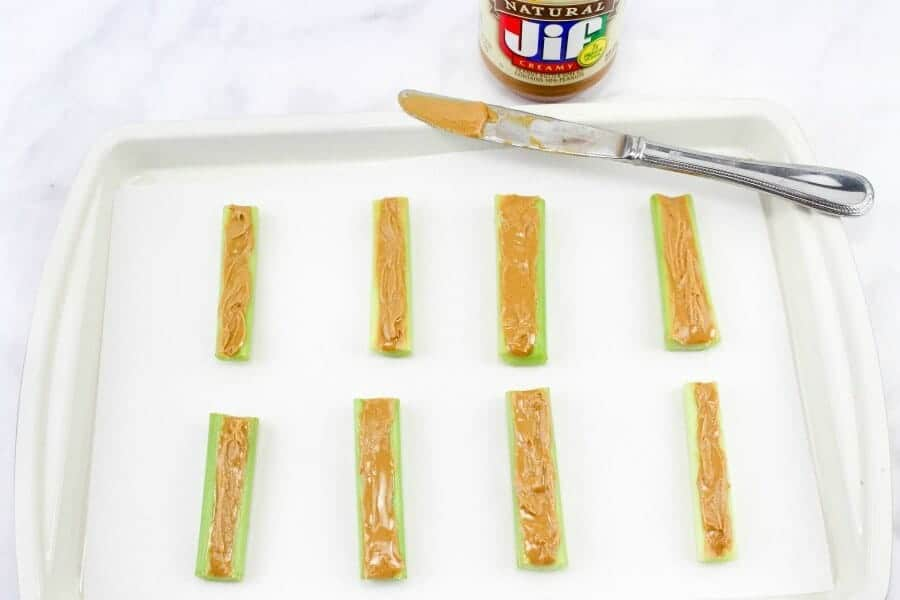 Eight slices of celery are on a platter covered in peanut butter. Above the celery is a jar of peanut butter and a knife covered in nut butter.