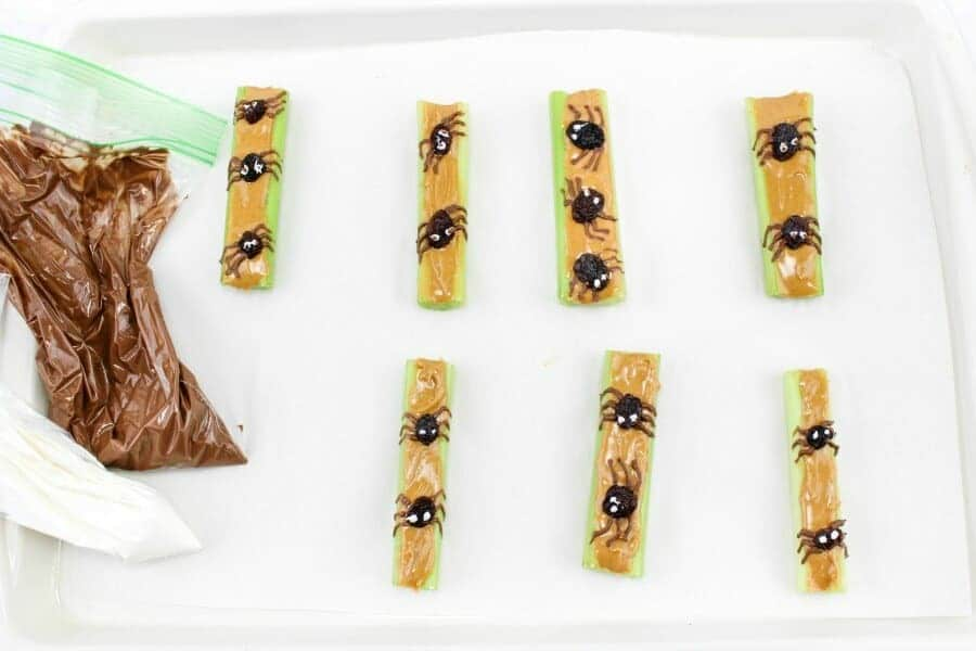 Peanut butter covered pieces of celery topped with raisins decorated like spiders with frosting on a pan