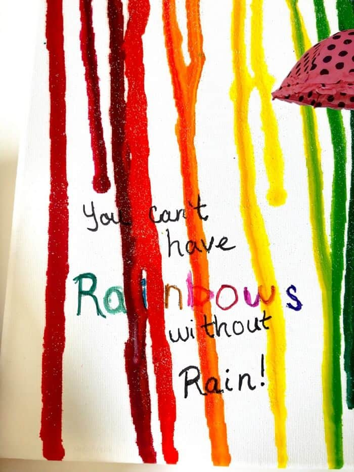 """Canvas that says \""""You can\'t have rainbows without rain with colorful melted crayon on top"""
