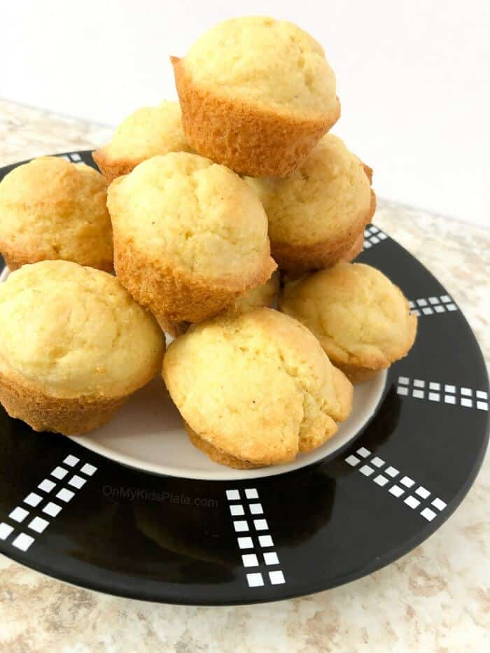 A pile of cornbread muffins sits high on a plate.