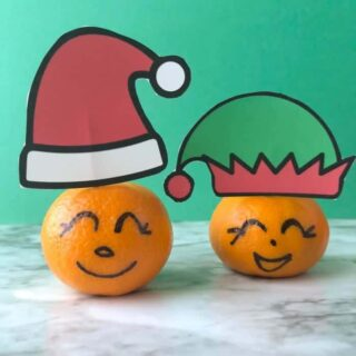 Clementines with faces drawn on the rinf and Santa and elf hats