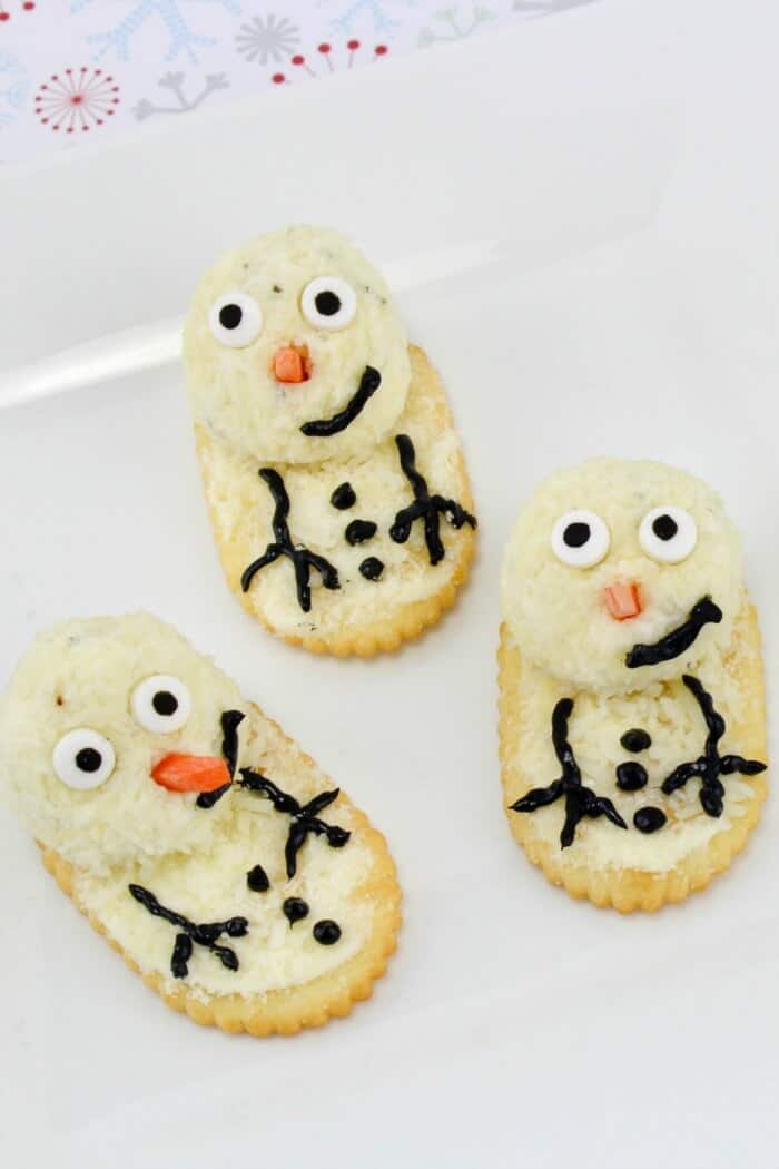 Several cheese and crackers decorated like snowmen on a plate.