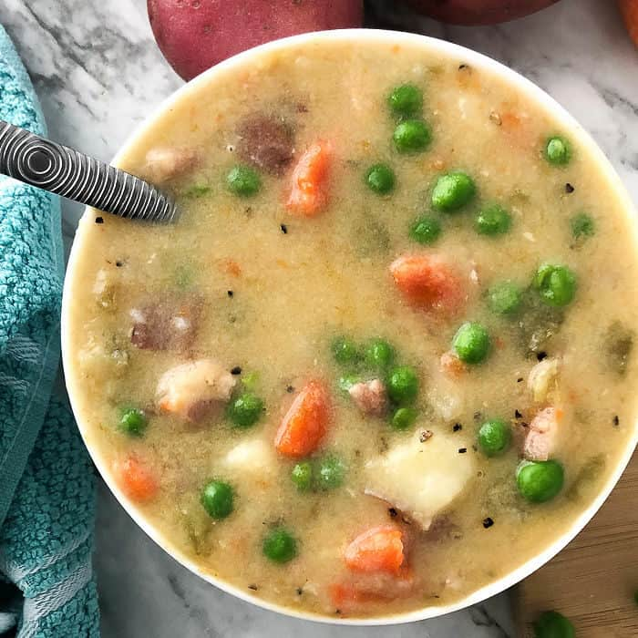 A bowl of potato soup with peas and carrots