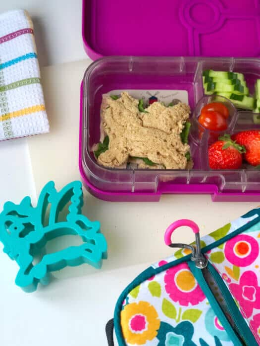 A child's bento lunchbox full of food including a sandwich shaped like a unicorn and a unicorn cookie cutter.