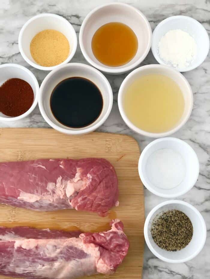 Two raw pork tenderloins on a cutting board surrounded by small bowls of spices and sauce ingredients.