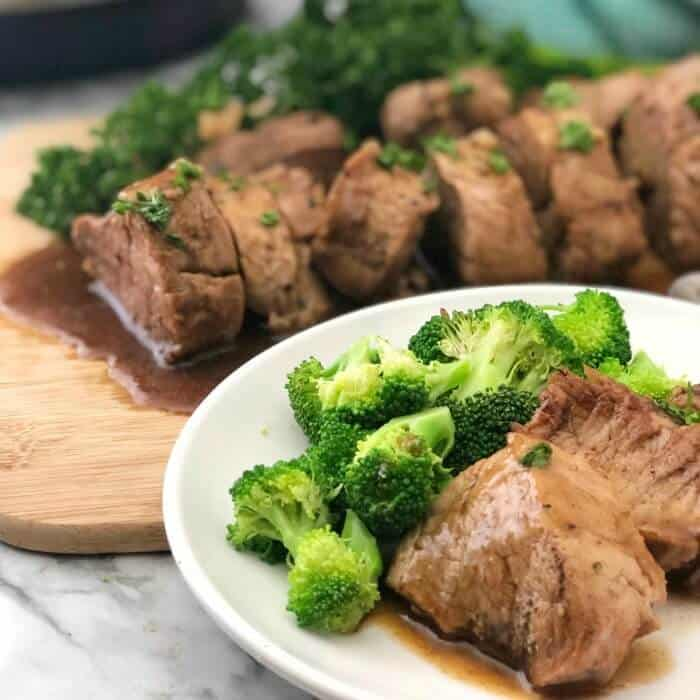 a plate of pork in sauce with broccoli, a cutting board filled with sliced pork behind the plate.