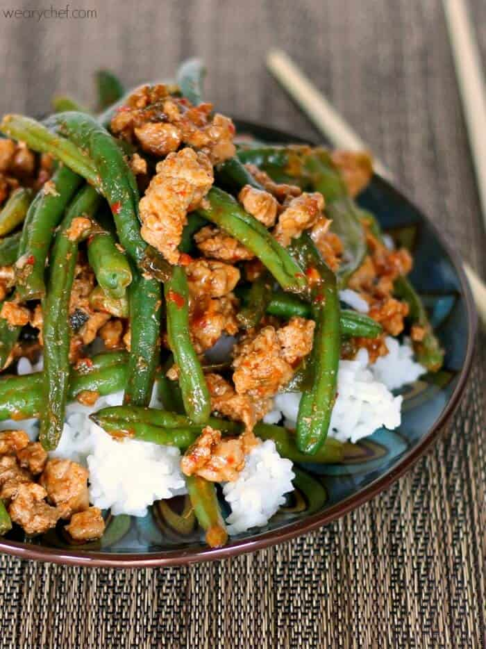 A plate of rice with stir-fried turkey and green beans on top.