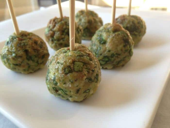 Small meatballs with spinach on toothpicks on a platter.