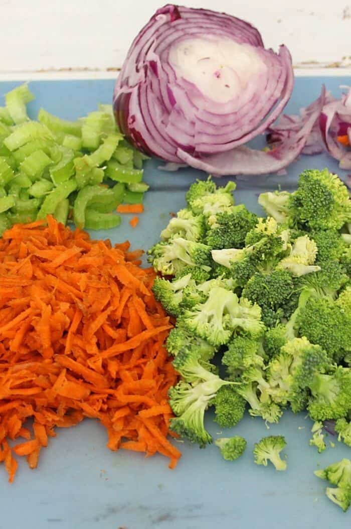 Carrots, celery purple onion and broccoli all sit on a cutting board chopped and ready to add to the broccoli apple salad with pasta bowl.