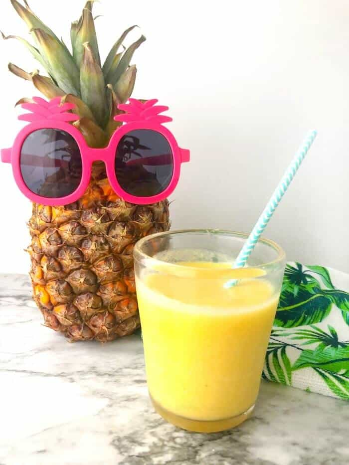A glass of yellow smoothie with a straw next to a pineapple wearing kid\'s pineapple sunglasses.