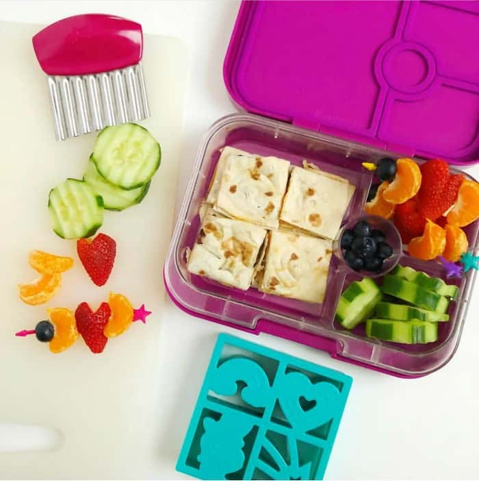 A kid\'s bento lunchbox filled with a quesadilla cut into shaped, cucumbers, blueberries and strawberry clementine skewers