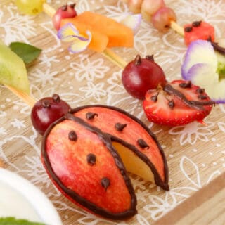 A plate of fruit skewers decorated and shaped like lady bugs and other insects