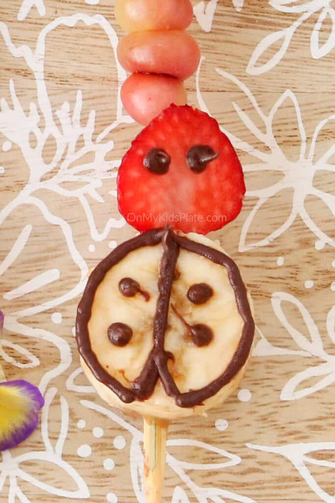 A lady bug made of banana, strawberry and chocolate on a skewer close up