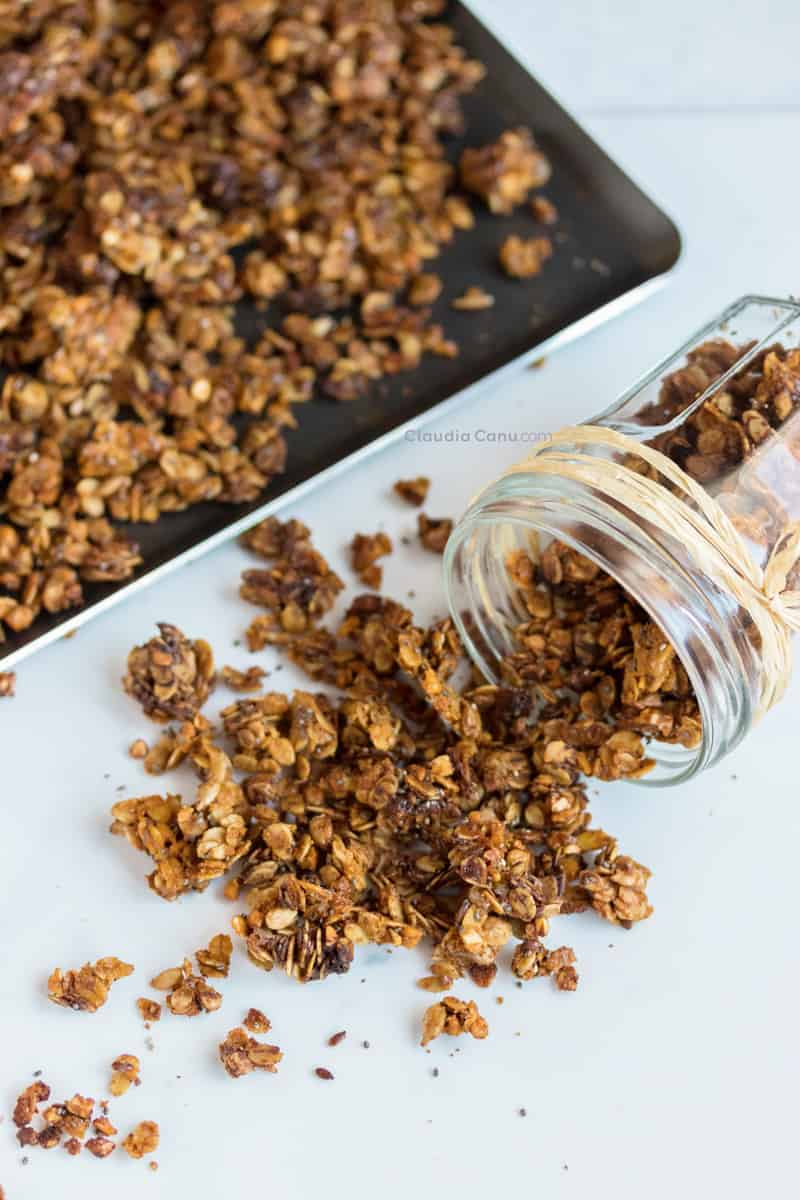 granola spilling out of a glass jar next to a baking sheet full of granola