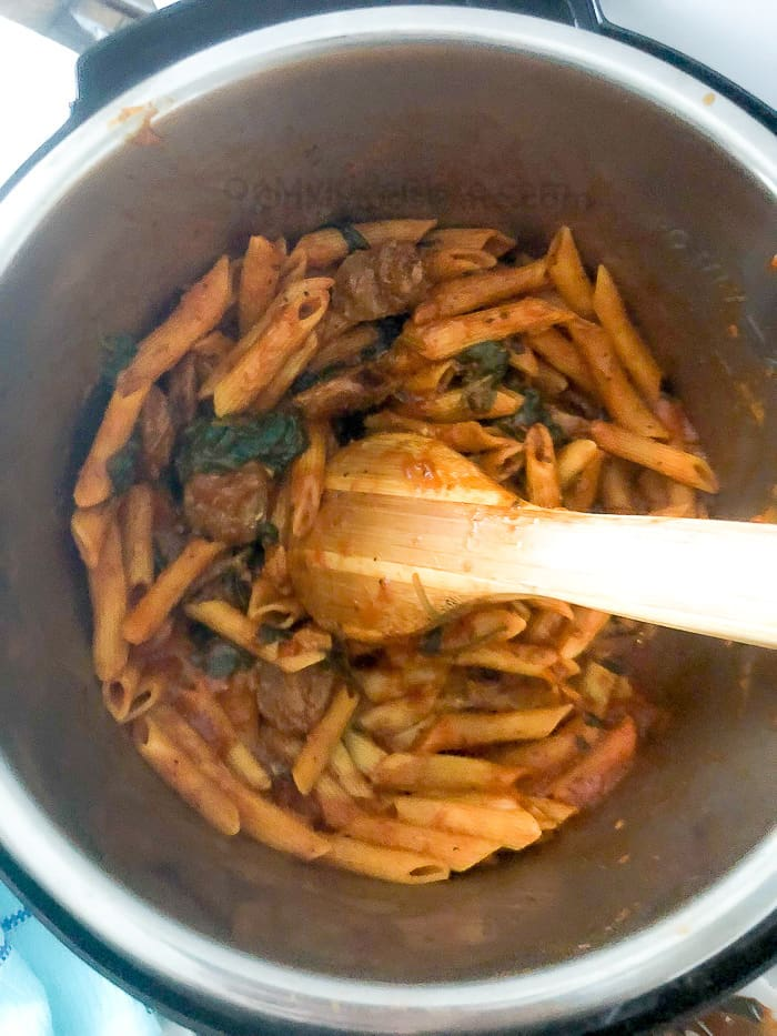 An above view of an instant pot full of pasta being stirred with a wooden spoon