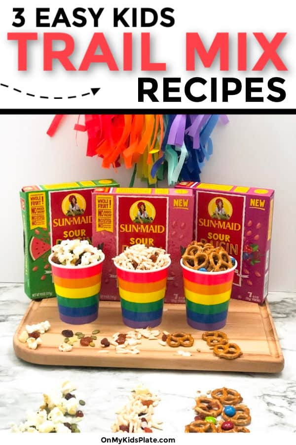 Three different rainbow cups of different trail mixes on a cutting board next to three boxes of flavored raisins with text title overlay