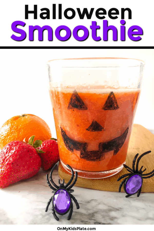 Close up of a jack o lantern glass full of orange smoothie next to fruit and spide rrings