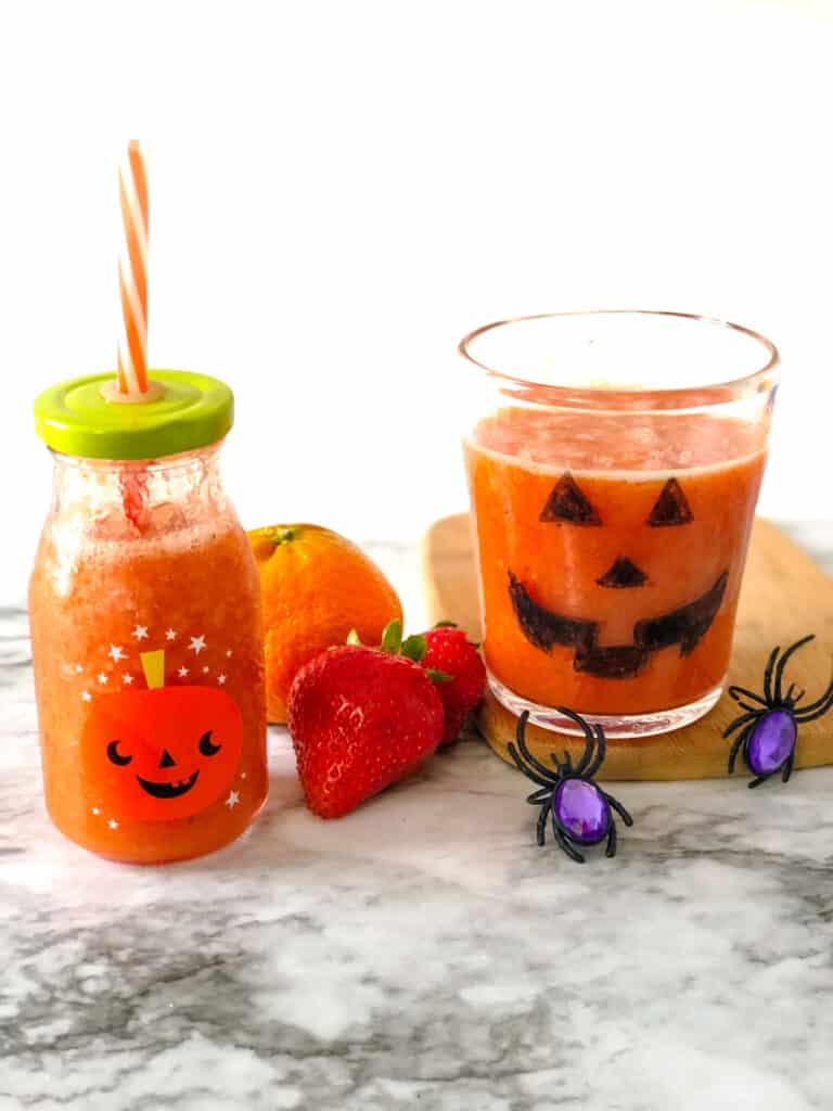 orange smoothie in a cup and milk glass decorated like pumpkins next to oranges and strawberries and spider rings