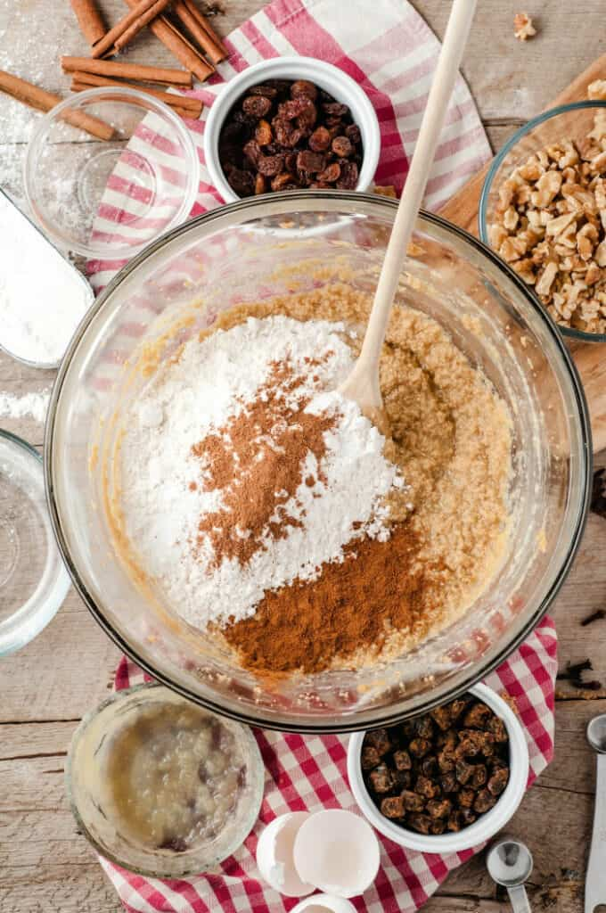 A large bowl full of apple cake batter sits with flour and spices on top ready to be mixed together.