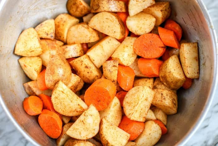 Chopped potatoes and carrots uncooked close up in a bowl with seasoning