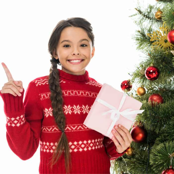 A little girl holding a present and standing next to a Christmas tree pointing to the side