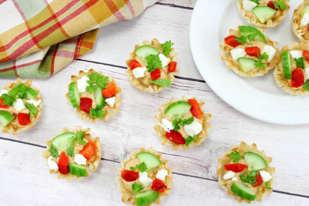 Party snack appetizers full of hummus, cucumber, red pepper and feta cheese on a table and plate