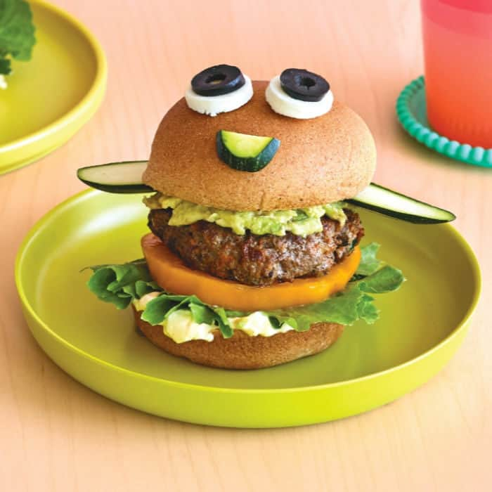 A beef burger made to look like a funny face on a plate