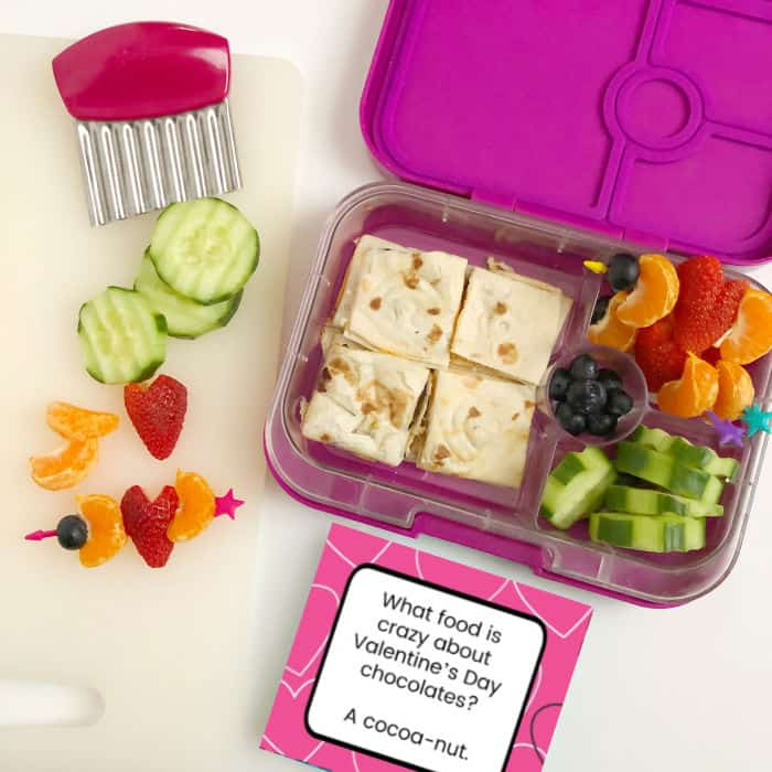 A kid\'s bento lunchbox full of quesadilla, cucumbers, blueberries, oranges and strawberries shaped like hearts with a lunchbox joke