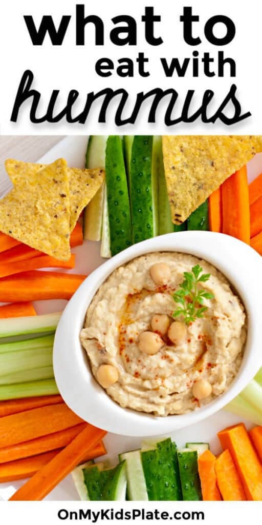 Hummus in a bowl on a platter with vegetables and chips