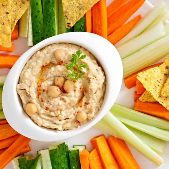 Hummus in a bowl with vegetables and tortilla chips