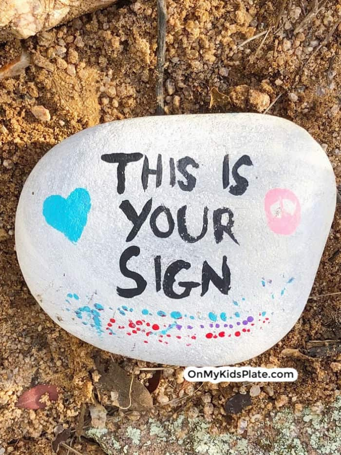 A picture of a painted rock that reads this is your sign.