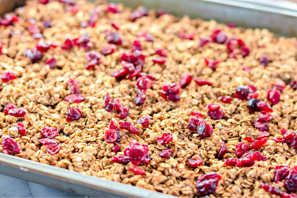 Baking pan full of granola sprinkled with cranberries