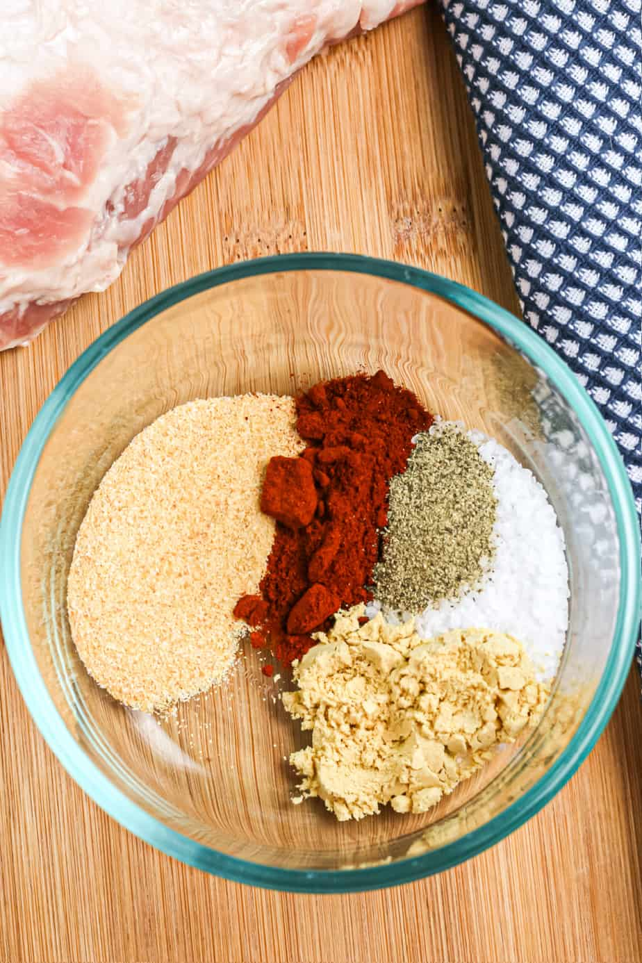 Spice rub in a bowl before mixed below a pork loin on a cutting board.