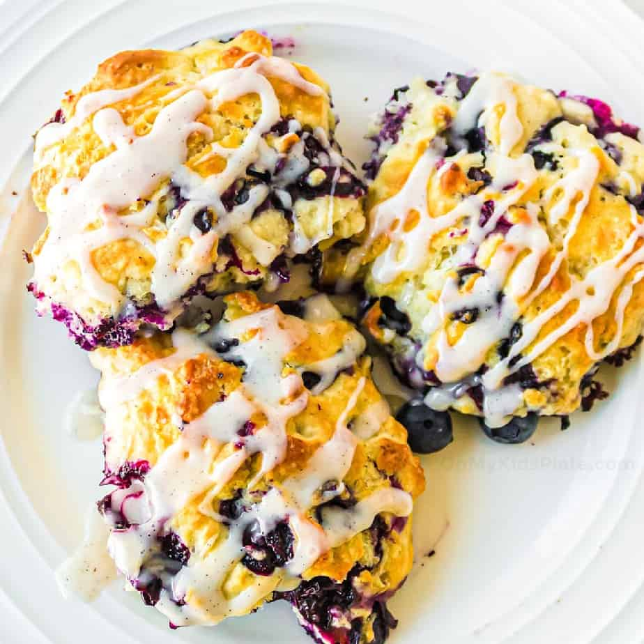 Three blueberry biscuits with glaze on a plate