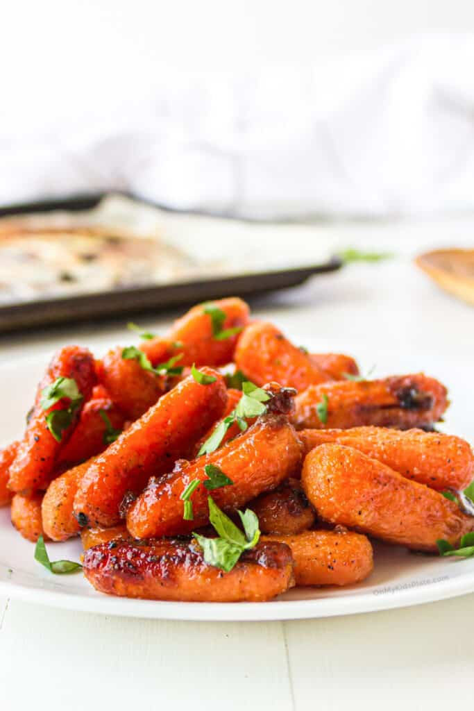 Baby carrots roasted with a shiny honey glaze on a plate from the side.