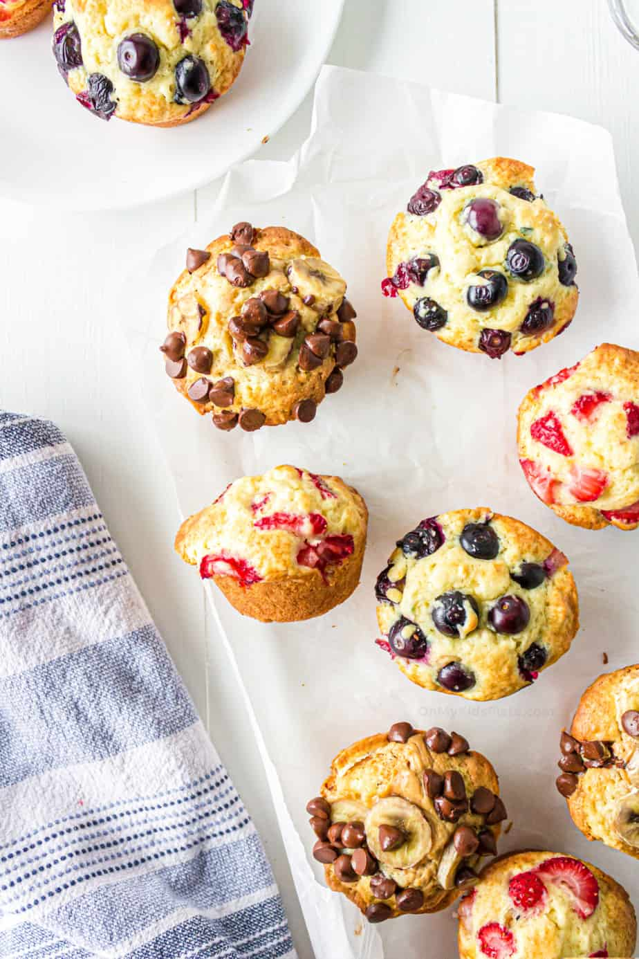 Strawberry, chocolate chip banana and blueberry muffins on parchment paper to serve.