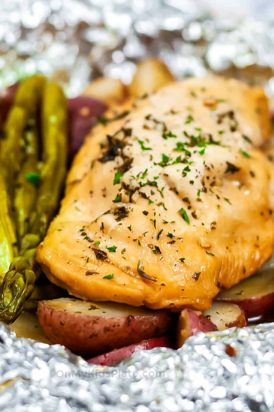 Close up of cooked chicken, asparagus and potatoes in a foil packet from the side.