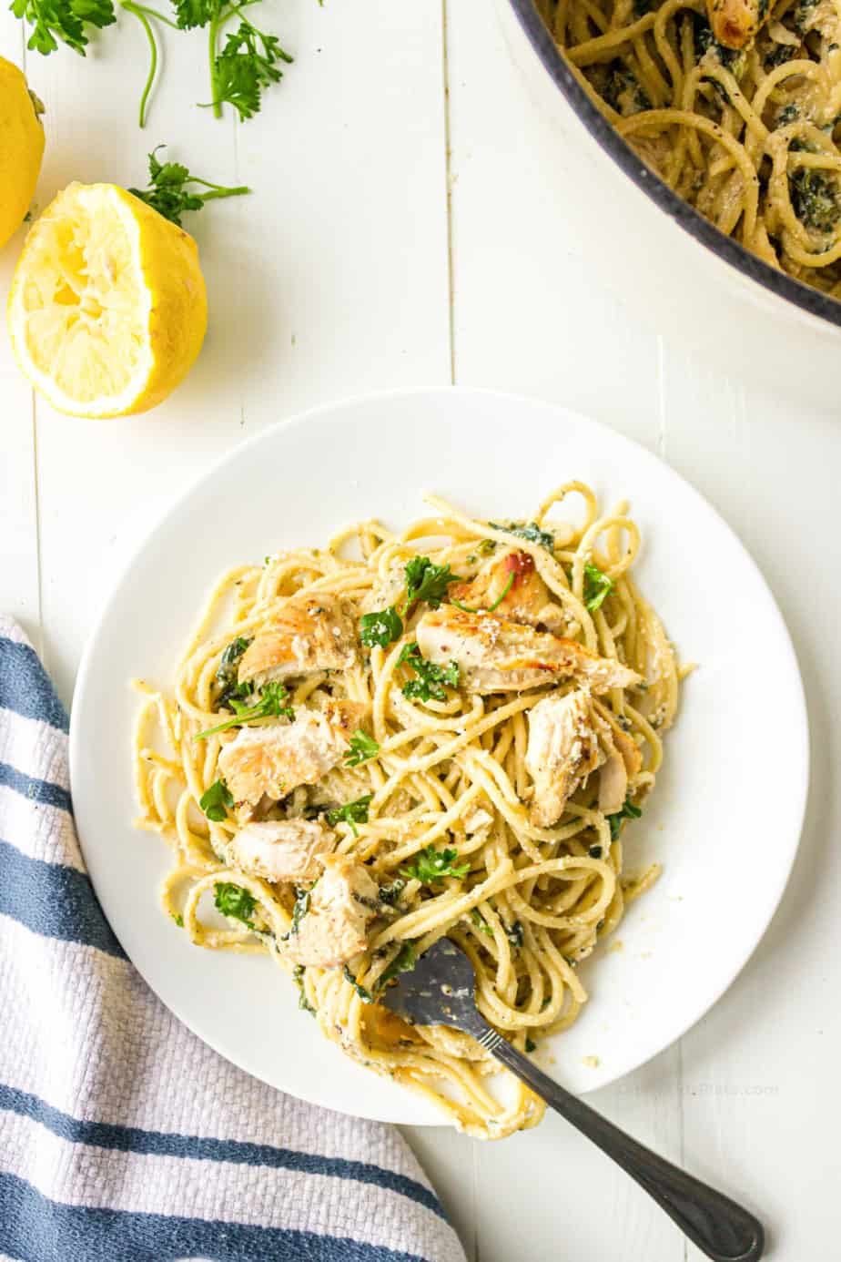 Spagehtti with chicken, lemon and herbs in a creamy sauce on a plate.