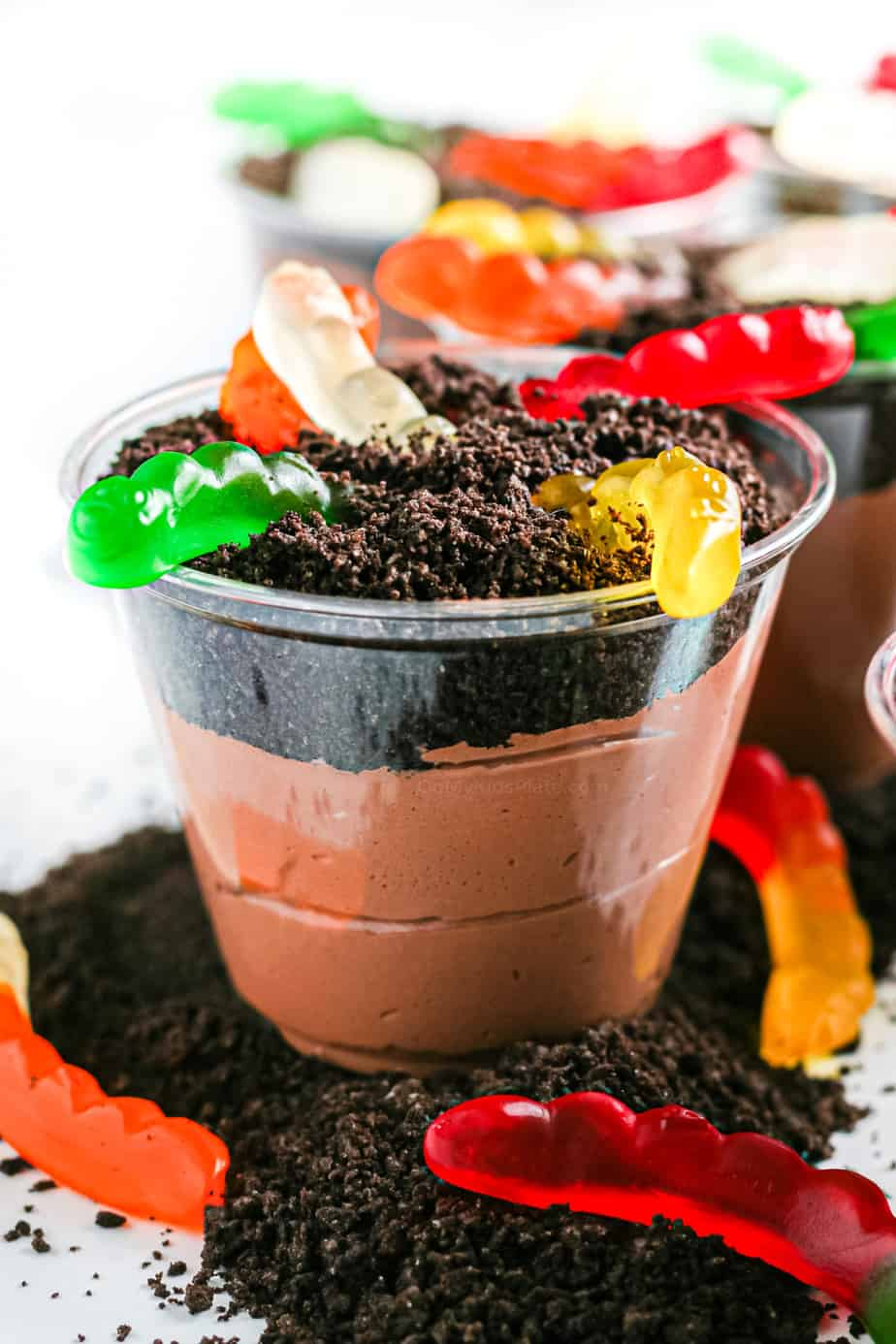 Chocolate pudding layered with oreo crumbs and gummy worms in a clear cup from the side