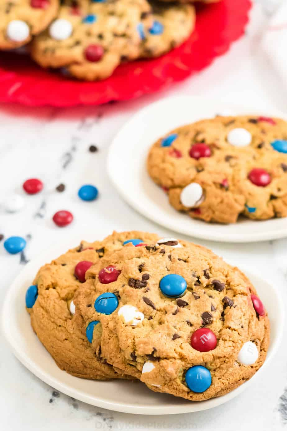Cookies with red white and blue M&Ms on two plates with a platter of cookies behind