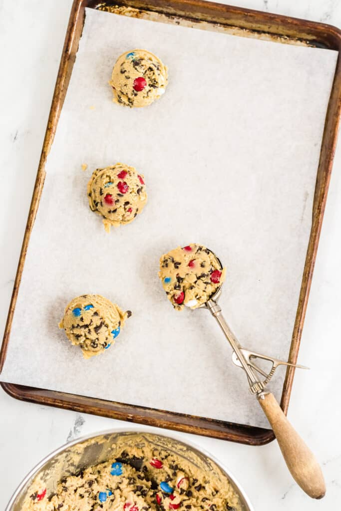 Cookie dough being scooped from a bowl to a baking sheet.