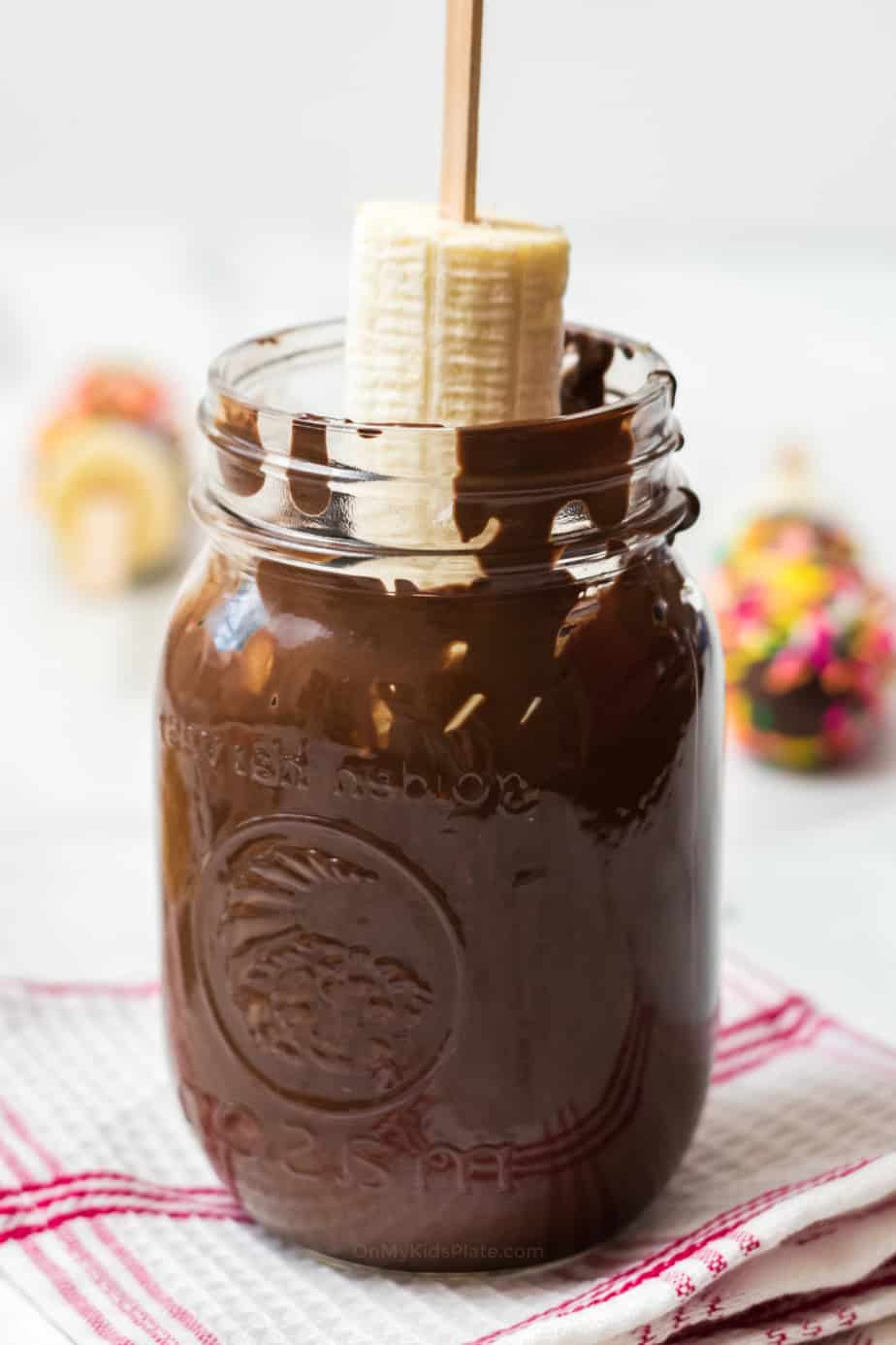 Banana on a stick being dipped in large jar of chocolate.