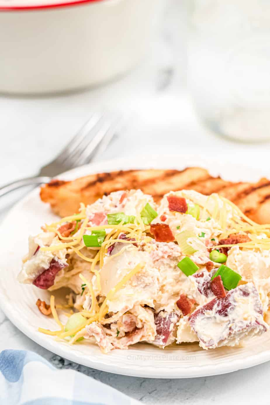 Loaded potato salad topped with cheese, bacon and green onions on a plate with grilled chicken